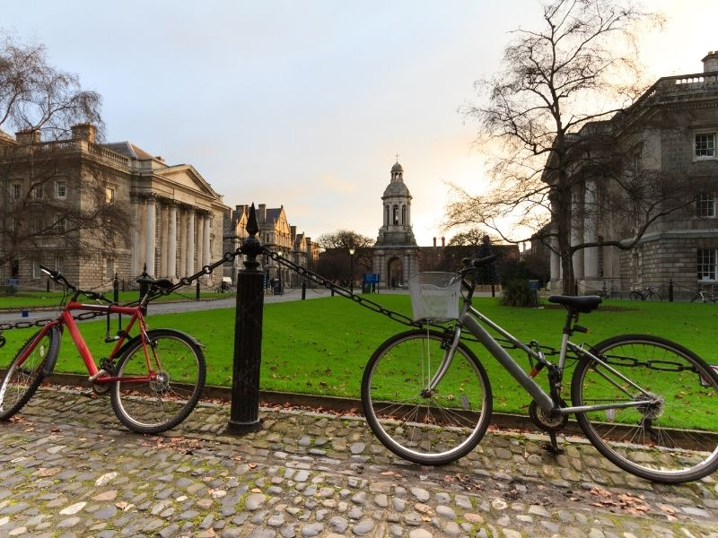 Two bicycles leaning against a railing on the cobblestone square at Trinity College Dublin
