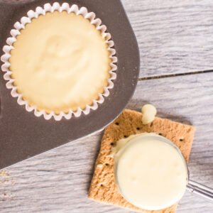 A spoon of cheesecake batter resting on a graham cracker beside a mini cheesecake in a muffin tray before baking.