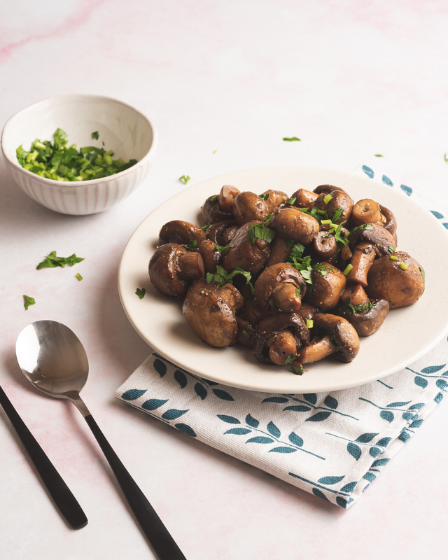 Fried mushrooms on a white dish with a bowls of parsley an a spoon