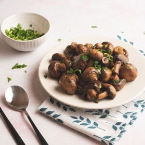 Golden brown sauteed mushrooms garnished with parsley and served on a white plate with a blue tree decorated napkin
