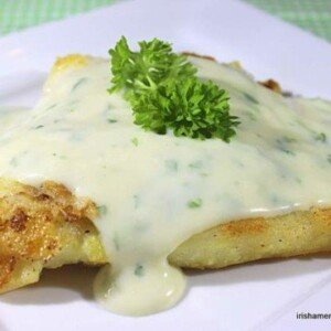 A portion of dredged and fried cod covered in a creamy parsley sauce