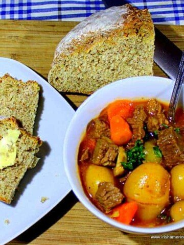 A bowl of beef stew with carrots, onions and potatoes in a white bowl served beside buttered lies of brown bread and a wedge of brown bread
