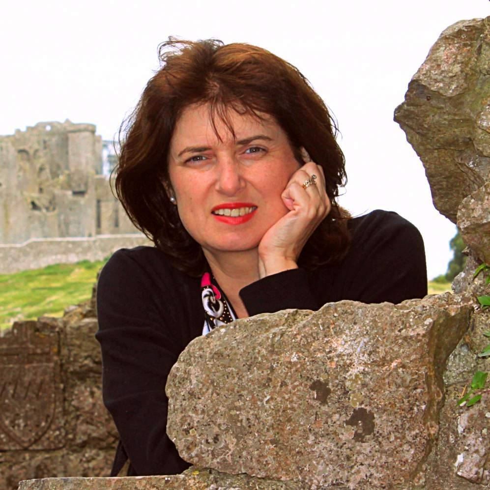 Face shot of a dark haired Irish woman leaning on a rock wall