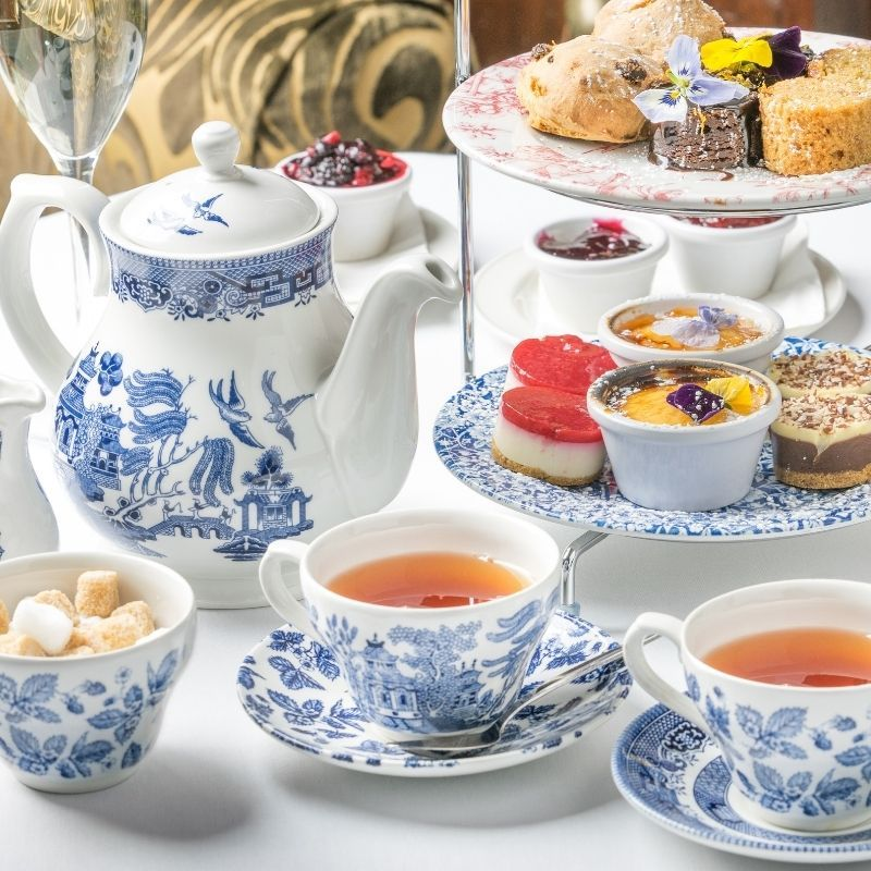 Blue and white willow pattern tea set with tea poured in two cups and a tiered cake stand with small afternoon tea cakes