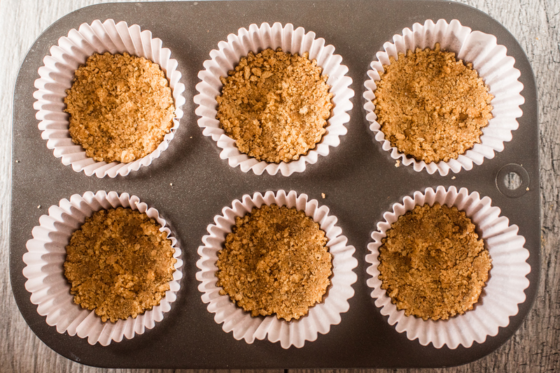A six place muffin pan with paper lines with a layer of graham cracker crumbs at the base