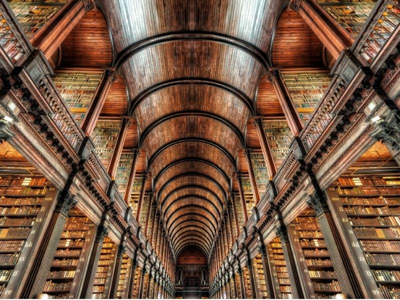 An arched wooden ceiling with walls lined with old books in the Old Library in Trinity College