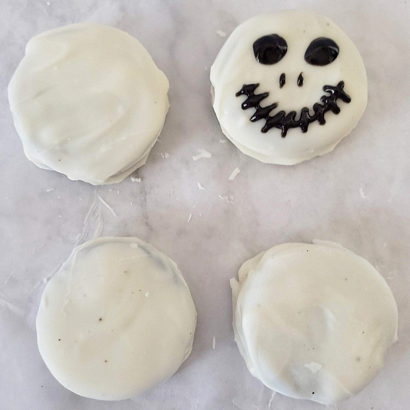 Using black gel icing to create a scary skeleton face on a chocolate dipped cookie