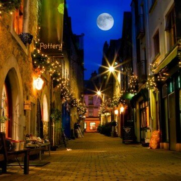 A full moon between the buildings of an Irish street