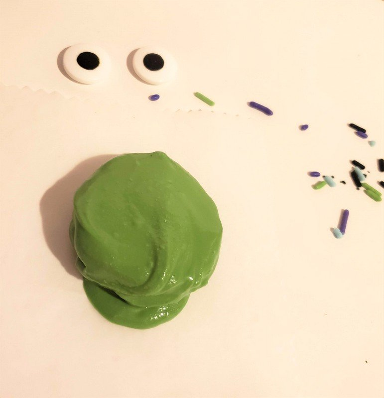 A cookie covered in green melted chocolate setting on white parchment paper