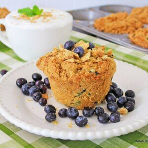 A blueberry muffin with a crunchy topping on a white plate beside a creamy coffee in a white cup