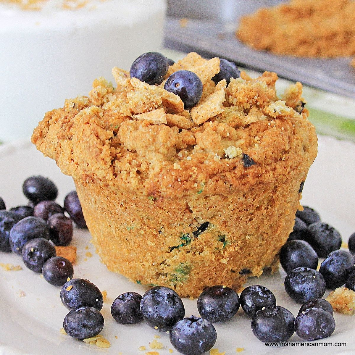 A jumbo sized blueberry muffin with streusel on a plate surrounded by blueberries