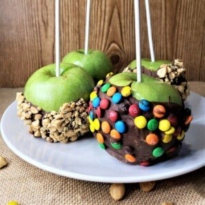 Four green apples half coated in chocolate and two dipped in candies and two dipped in crushed nuts
