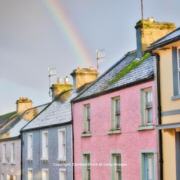 A rainbow over rooftops of brightly painted houses