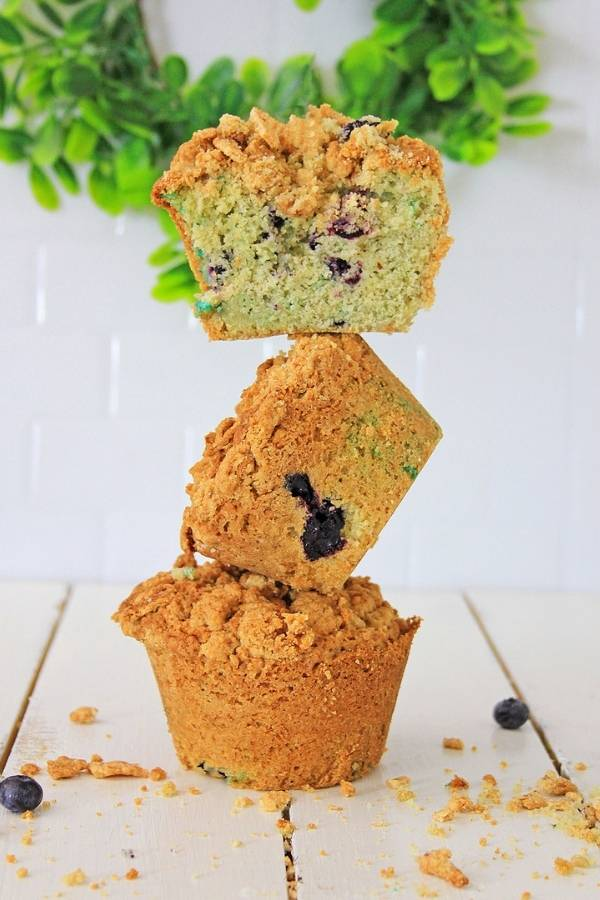 Blueberry muffins balanced on each other for a photo shoot with the top muffin cut in half