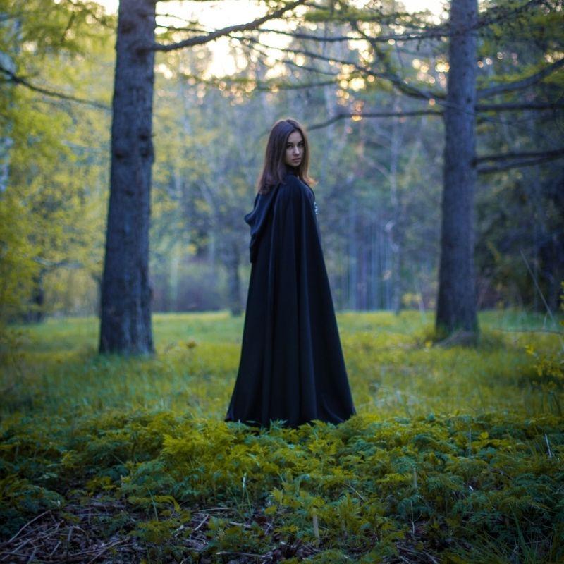 A girl in a black cloak standing in a forest