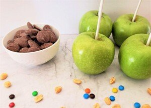 Ingredients for chocolate dipped apples include apples on lollipop sticks, chocolate melts, and peanuts and colored button candies