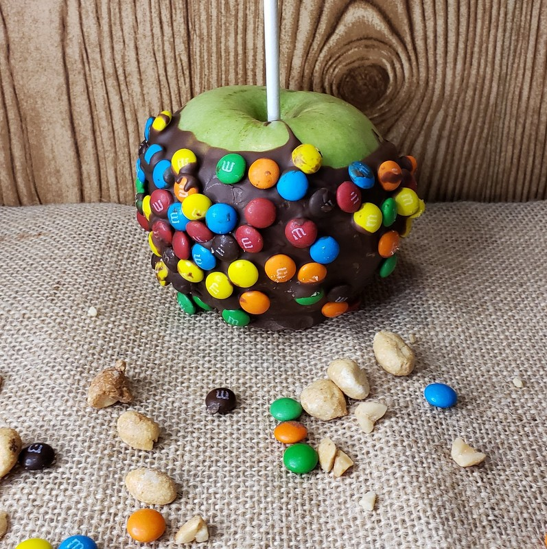 A green apple coated in chocolate and colored candies displayed on burlap with scattered nuts and candies