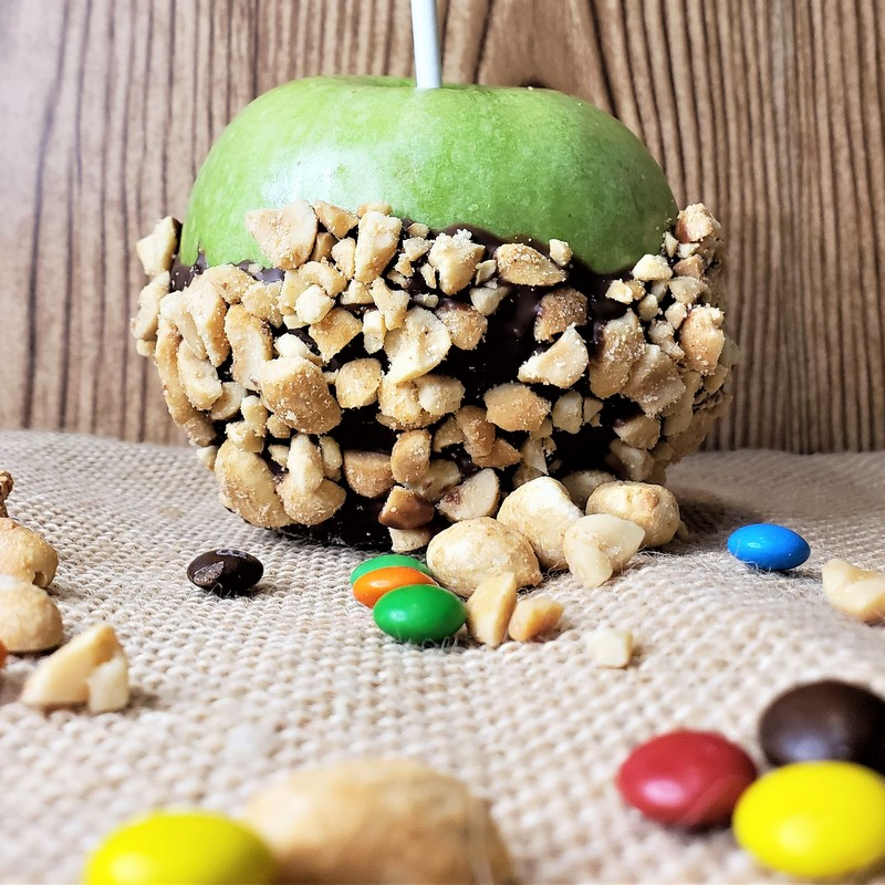 A green apple dipped in chocolate and crushed nuts displayed on burlap with scattered nuts and candies