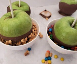 Green apples dipped in melted chocolate being coated in nuts and in candies in two white bowls