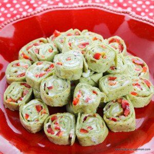 A red plate with a stack of festive pinwheel sandwiches with red peppers speckled through the filling