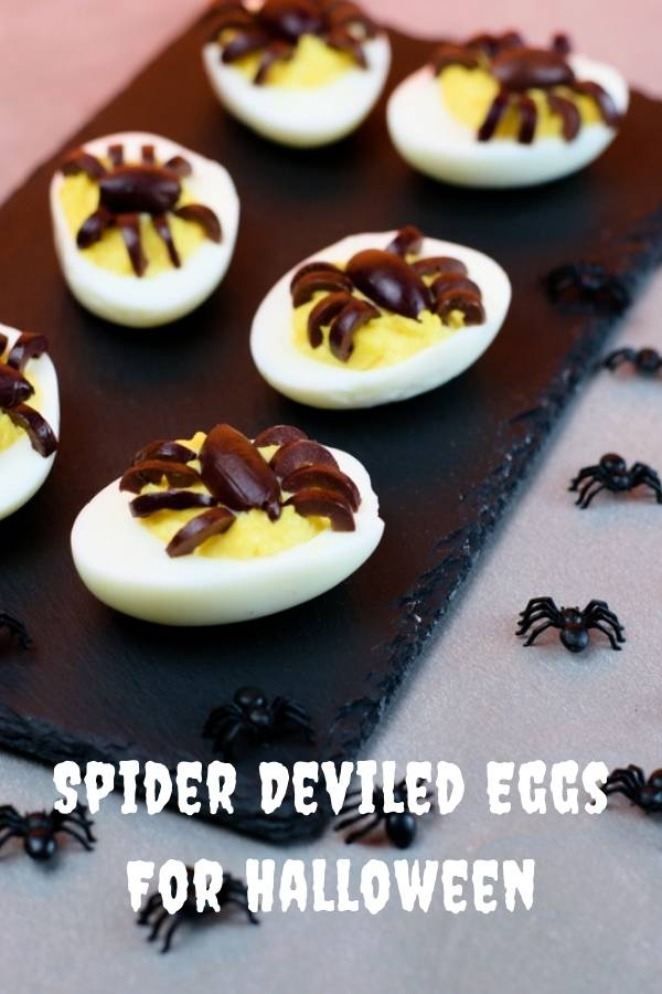 Spiders around deviled eggs served on a black slate and garnished with spiders made from black olives