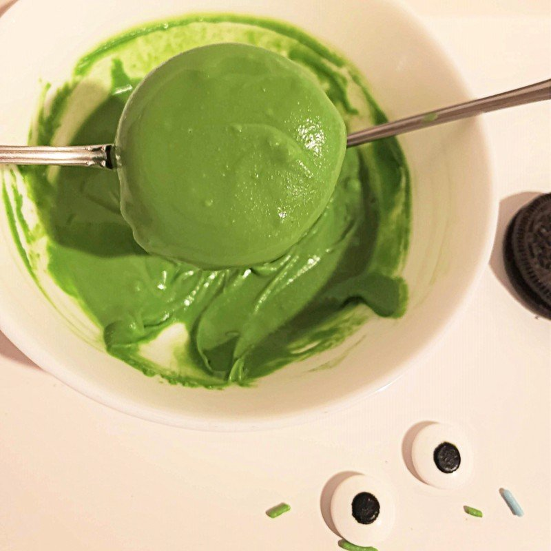 Using two forks to balance a cookie being coated in melted green candy melts