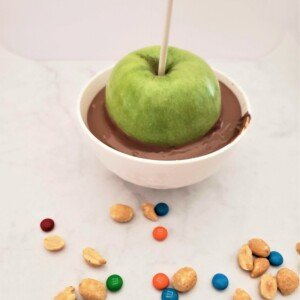 A green apple on a lollipop stick being dipped into a white bowl of melted chocolate