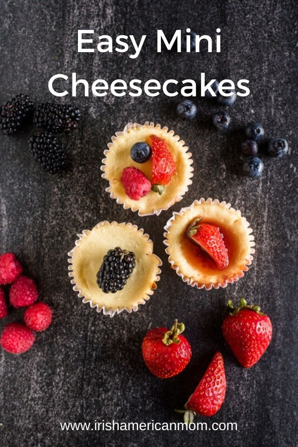 Three mini cheesecakes surrounded by fruit on a gray slate on a graphic for Easy Mini Cheesecakes