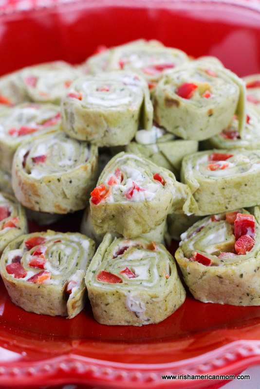 Red pepper filled party pinwheel sandwiches served on a festive red platter