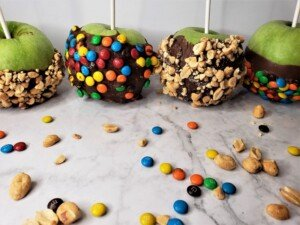 A row of chocolate dipped and decorated green apples with lollipop sticks inserted into them