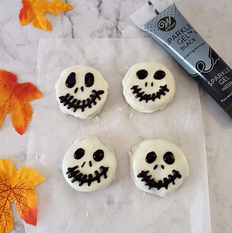 Using black gel icing to decorate white chocolate cookies for Halloween
