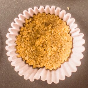 A layer of graham cracker crumbs in a muffin liner