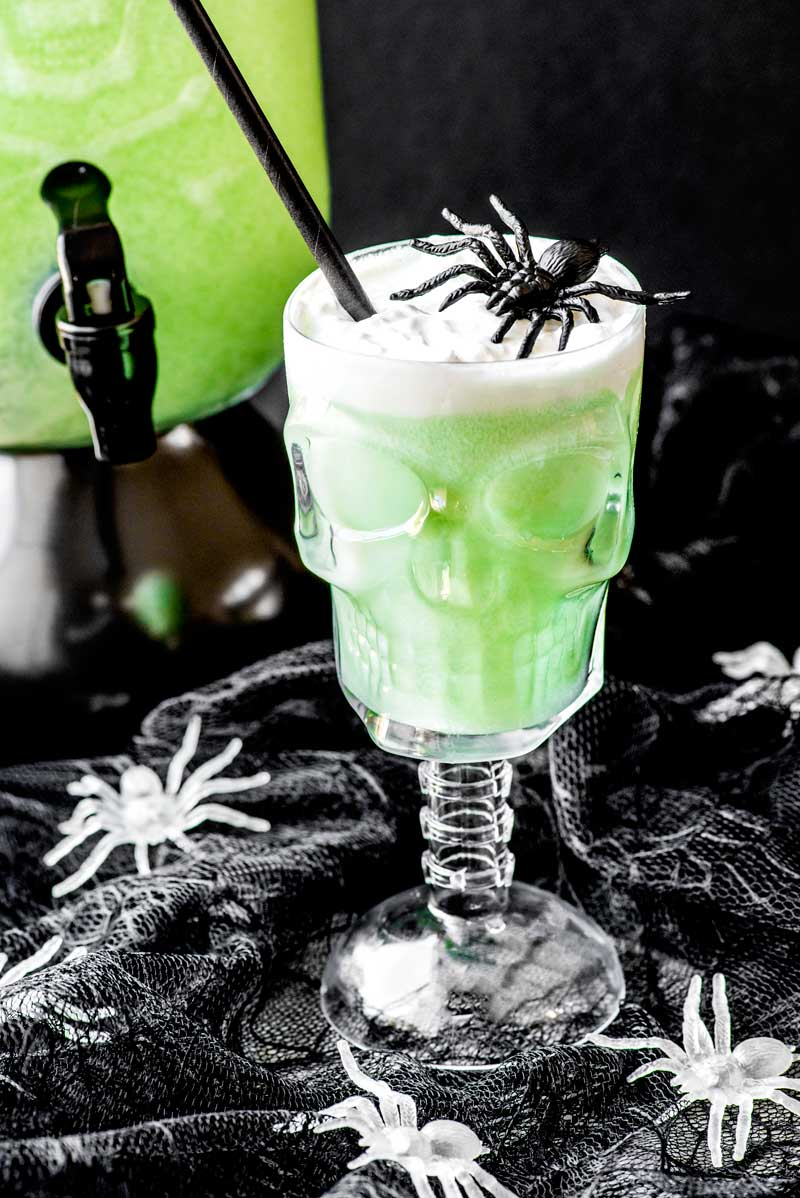 A skeleton glass filled with green potion and topped with a black spider and straw