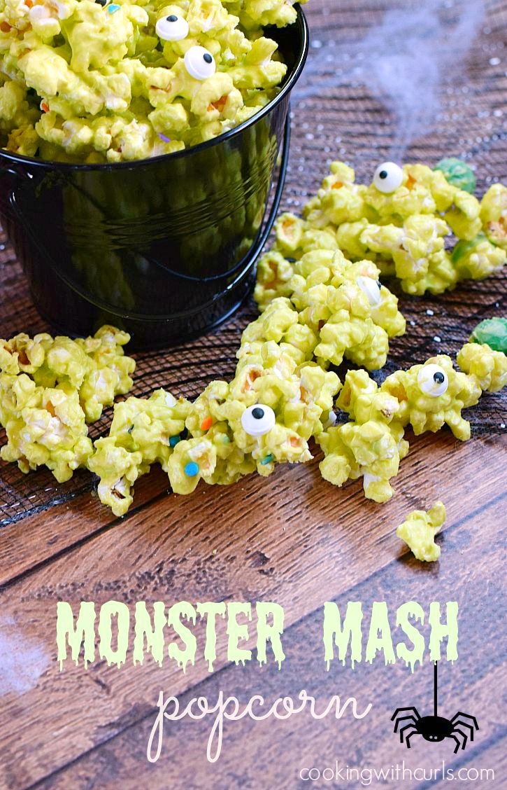 Green popcorn with eye decorations beside a black bucket bowl for Halloween