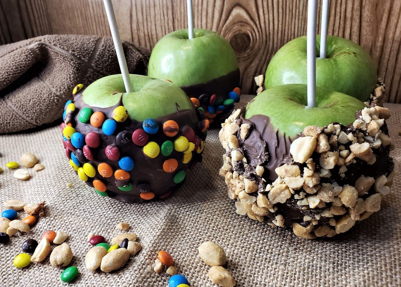 Four chocolate dipped and decorated green apples with lollipop sticks for serving