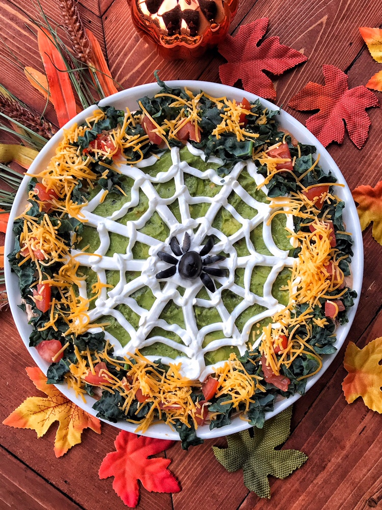 A green taco dip decorated like a spider web for Halloween