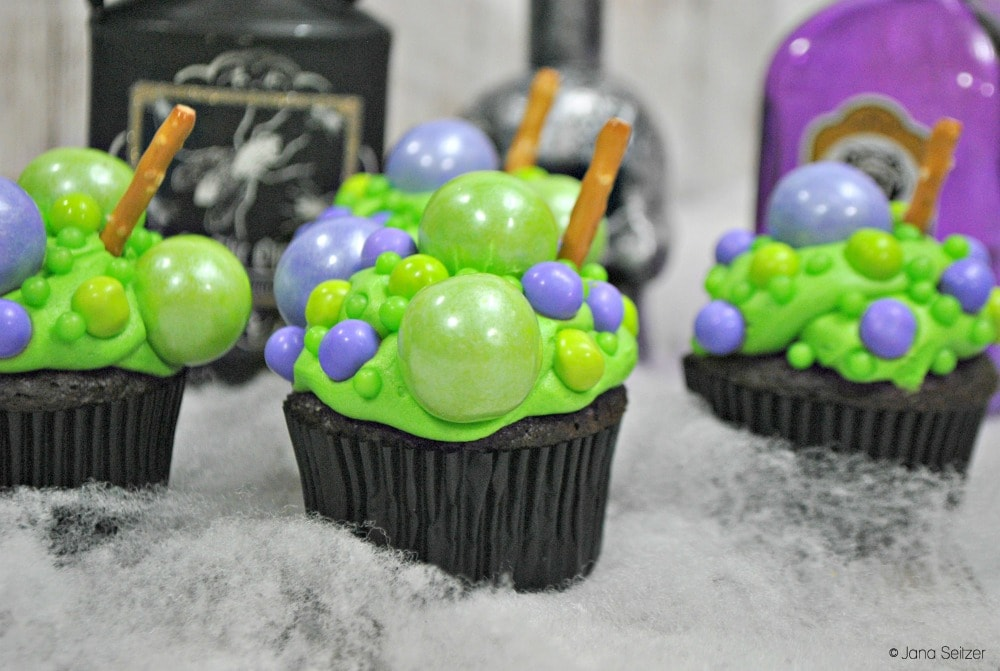 Chocolate cupcakes decorated with green and purple bubbles to look like a Hocus Pocus cauldron
