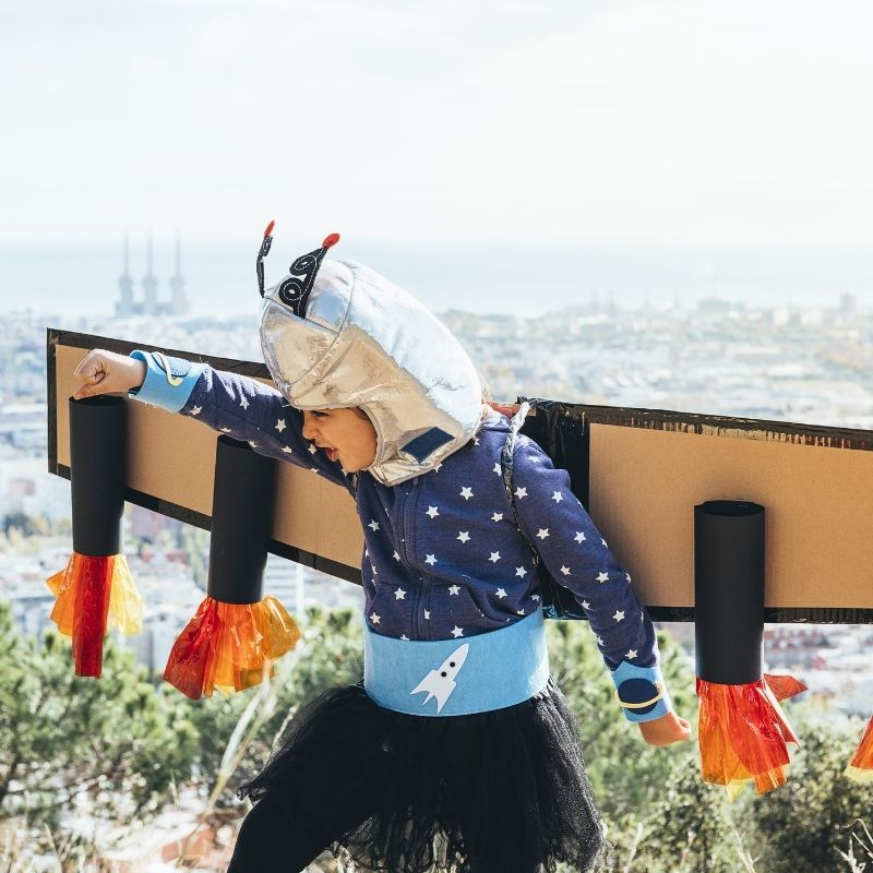 Homemade airplane costume featuring cardboard wings and black engines with orange paper flames