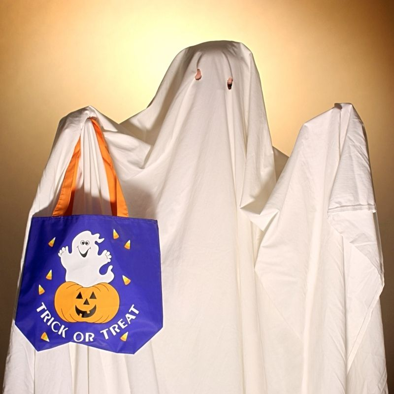 A sheet used as a ghost costume with eyes cut out while the person holds a trick or treat bag aloft