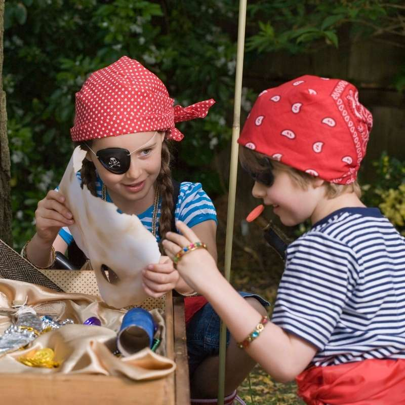Two children wearing striped shirts and red pirate bandanas examine a treasure map