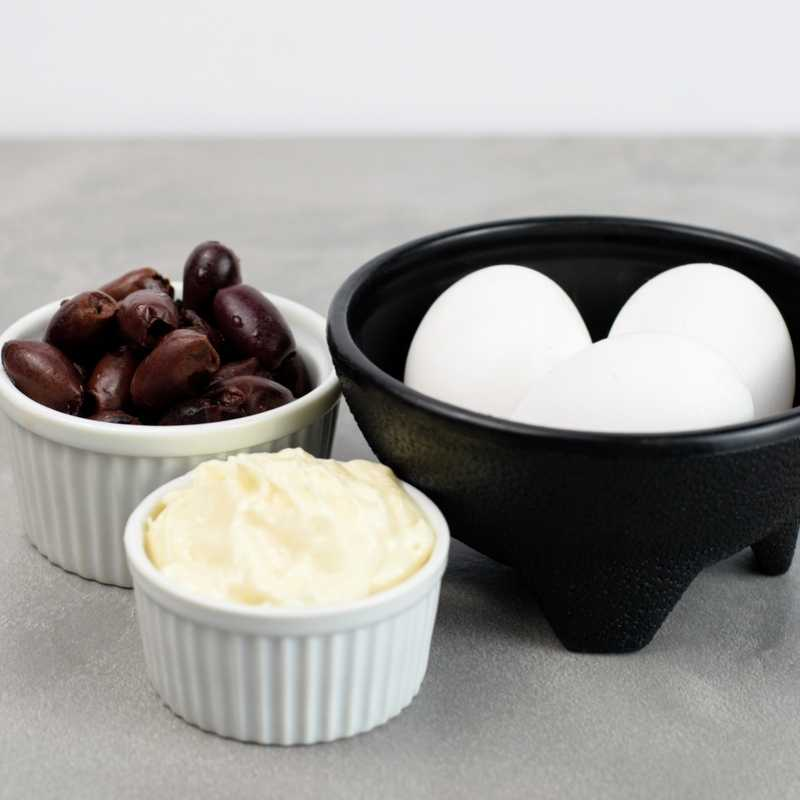 Eggs in a black bowl, beside a small bowl of olives and mayonnaise