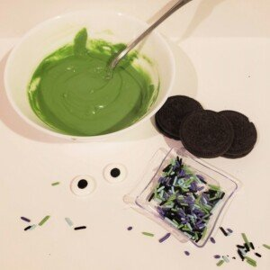 A bowl of melted green candy melts, Oreo cookies, candy eyes and purple, green and black sprinkles