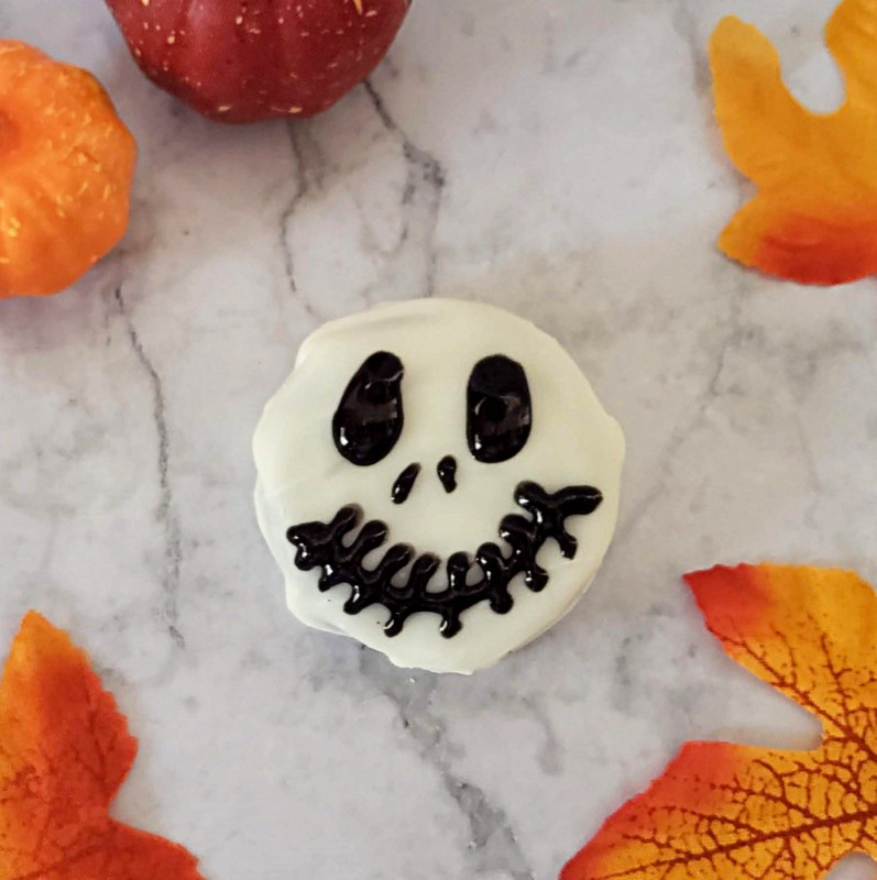 A white chocolate dipped cookie with a black skeleton face traced with black gel icing
