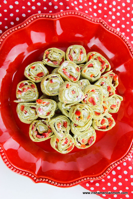 Looking down on a festive red platter of Christmas party pinwheel tortilla roll up sandwiches