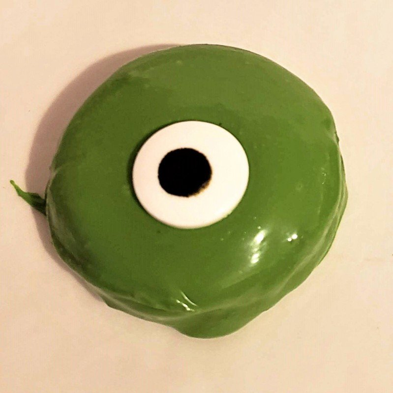 A green chocolate covered cookie with a white and black candy eyeball placed in its center
