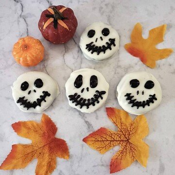 Black skeleton faces on white chocolate dipped cookies displayed beside fall leaves and miniature decorative pumpkins
