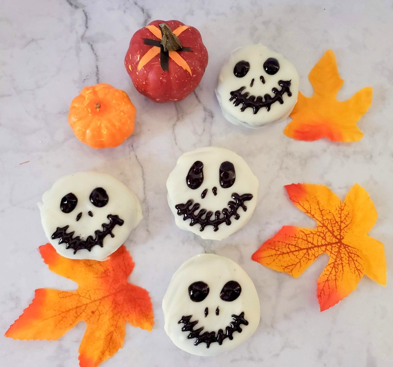 Autumn leaves and decorative pumpkins around four skeleton faced chocolate dipped cookies on a marble display