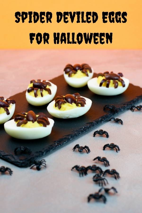 A black slate serving six deviled eggs with spiders made of olives