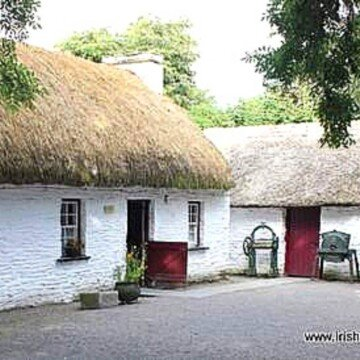 A yellow thatched roof on a white washed cottage beside a thatched shed with a red door
