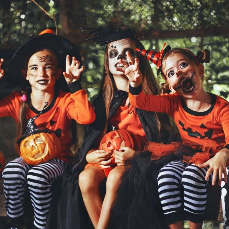 Three children in Halloween orange and black costumes waving while holding small carved pumpkins